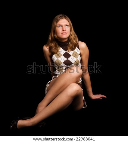 Cute girl sitting on the black background - stock photo