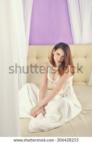 Cute girl sitting on the couch in the bedroom. The concept of home comfort. - stock photo