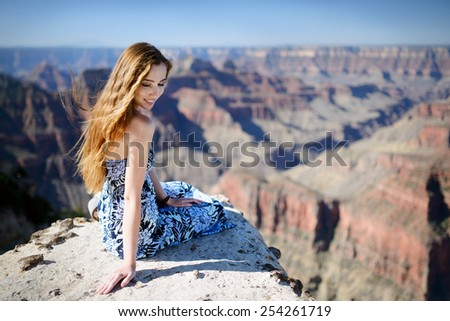 Cute girl sitting on the edge of picturesque cliffs of The Grand Canyon - stock photo