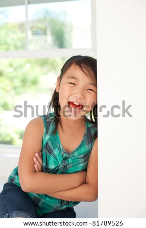 cute girl sitting on window and smiling