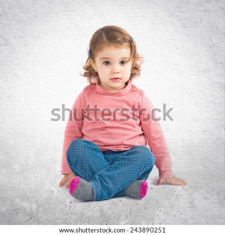 Cute girl sitting over textured background