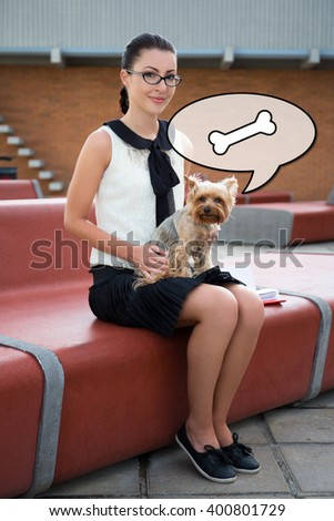 cute girl sitting with dog yorkshire terrier in city park - stock photo
