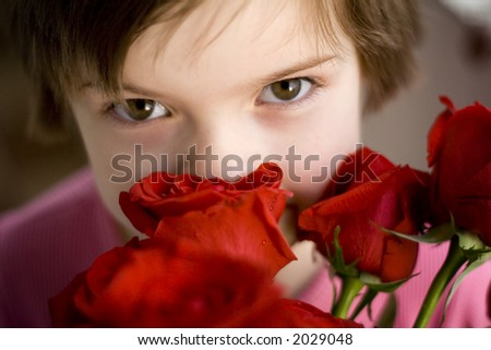 Cute girl smelling red roses - stock photo