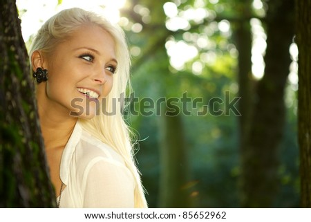 Cute girl standing against a tree in a green park. - stock photo