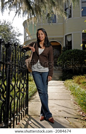cute girl standing by gate in front of home - stock photo