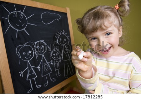 Cute girl standing in front of blackboard. Holding chalk. Smiling and looking at camera - stock photo
