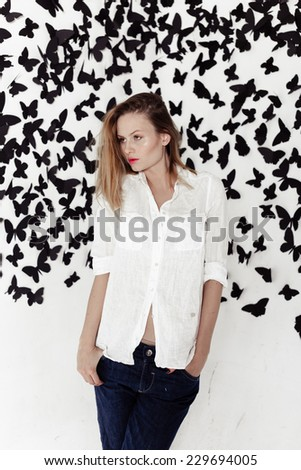 Cute girl standing on a fantastic background with lots of butterflies on a white wall - stock photo