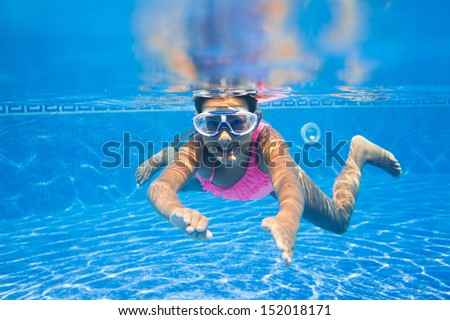 Cute girl swimming in pool underwater and smiling - stock photo