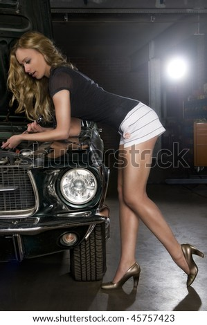 cute girl taking a look into the engine block - stock photo