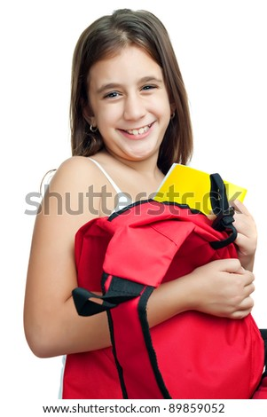 Cute girl taking her textbook out of a bright red backpack isolated on a white background