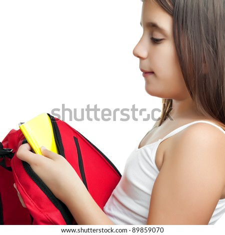 Cute girl taking her textbook out of a bright red backpack isolated on a white background - stock photo