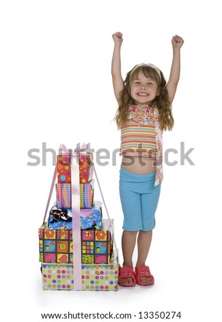 Cute girl throwing arms in the air with excitment, standing next to a stack of presents, white background. - stock photo