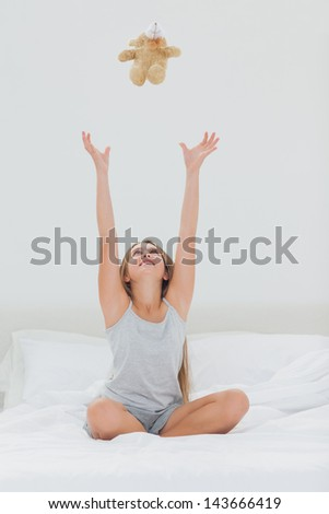 Cute girl throwing her teddy bear in the air while she is sat in her bed - stock photo