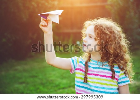 Cute girl throwing paper airplane at summer park. Happy childhood, travel, vacation concept. - stock photo