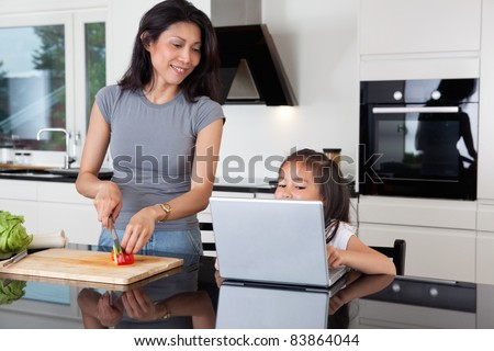Cute girl using laptop while mother cuts vegetable in kitchen - stock photo