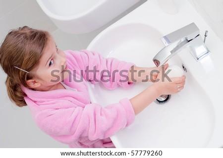 Cute girl washing hands - stock photo