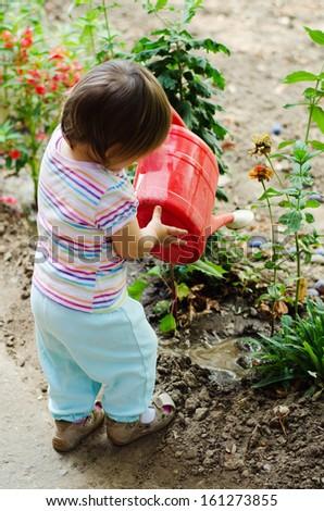 Cute  girl watering flowers in the garden - stock photo