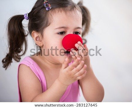 Cute girl wearing clown nose at home - stock photo