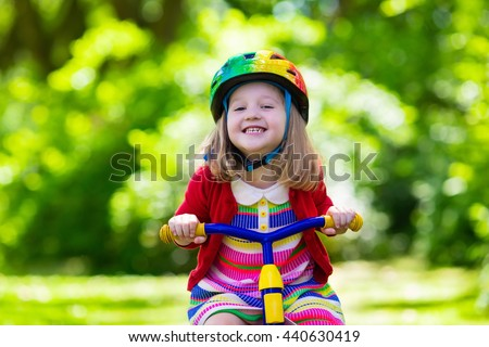 Cute girl wearing safety helmet riding her tricycle in sunny summer park. Kids ride bicycle. First bike for little child. Active toddler kid playing and cycling outdoors. Kids play in the garden. - stock photo