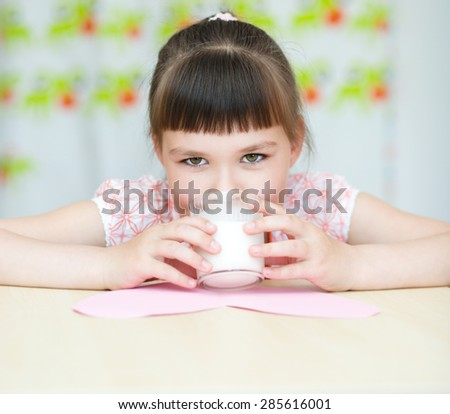 Cute girl with a glass of milk - stock photo