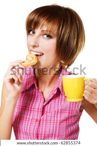 Cute girl with a tea cup biting a pretzel, white background