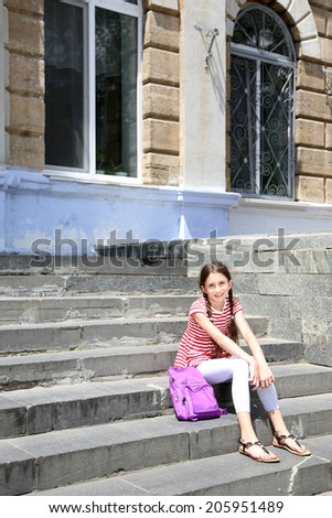 Cute girl with backpack on the steps outside  - stock photo