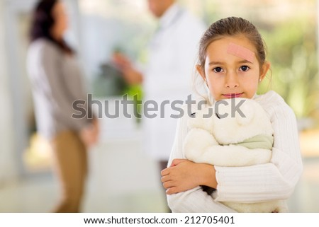 cute girl with bandage on her face holding a teddy bear in doctors office - stock photo