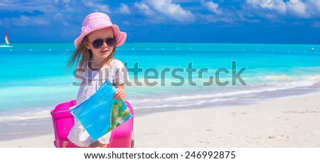 Cute girl with big luggage on white beach - stock photo