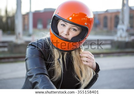 Cute girl with blond hair with orange motorcycle helmet. Outdoor, urban scene. - stock photo