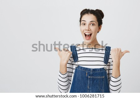 Cute girl with dark hair in hairbuns looking at camera having excited and happy facial expression, pointing her thumb fingers sideways at blank studio wall with copy space for promotional content