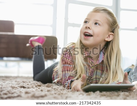 Cute girl with digital tablet looking away while lying on rug in living room - stock photo