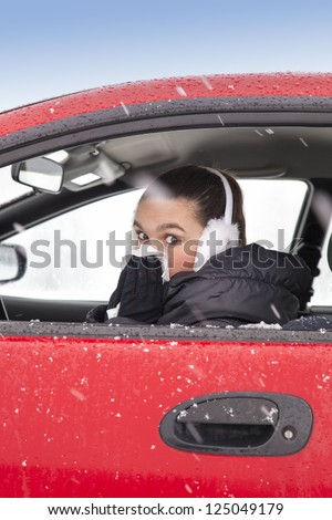 Cute girl with flu symptoms sneezes in a car on snowy  winter day. Using handkerchief closes mouth with her hands. - stock photo