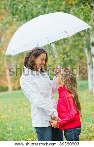 Cute girl with her mother with white umbrella walking in the autumn park. Rain, yellow leaves, tree.
