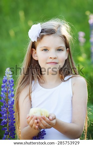 cute girl with little chicken outdoors - stock photo