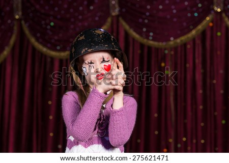Cute girl with old helmet and with a red heart painted on face pretending to have a gun in a conceptual play about war, love and innocence - stock photo