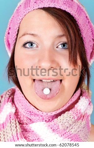 cute girl with one pill on her tongue - stock photo