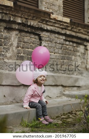 Cute girl with pink balloons urban portrait - stock photo