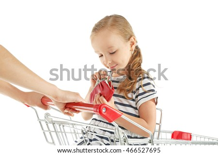 Cute girl with purse in hands sitting in shopping cart on white background