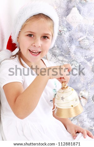 Cute girl with Santa hat holding Christmas bell - stock photo