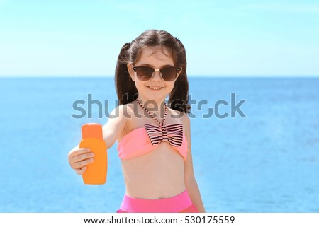 Cute girl with sun protection lotion on beach