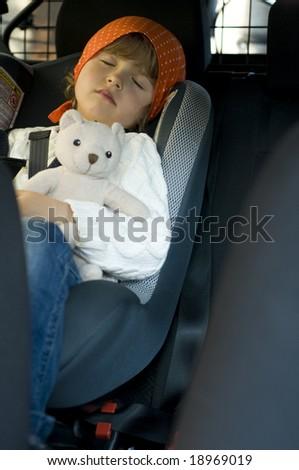 Cute girl with teddy bear  sleeping in belt seat - stock photo