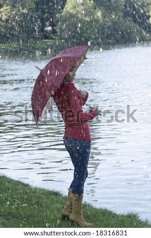 Cute girl with umbrella looking at the river in fall season