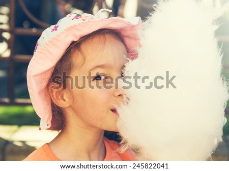 Cute girl with white cotton candy. Toned - stock photo