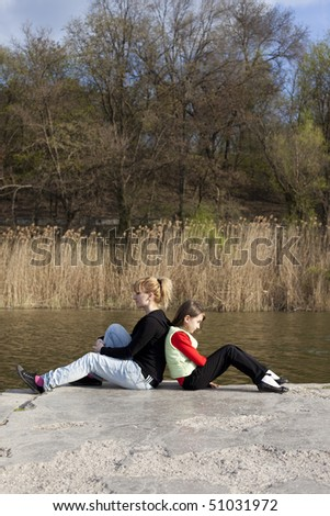 Cute girl with woman sitting near a lake