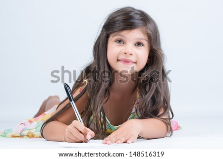 Cute girl writing a letter on the floor and looking at camera
