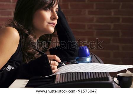 cute girl writing on piano at wall - stock photo