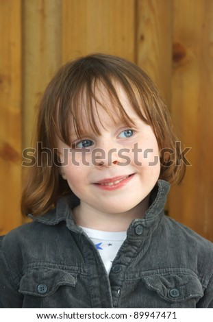 Cute girl (4yr) against a wooden background - stock photo