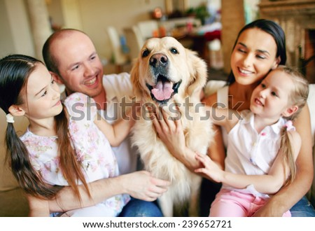 Cute girls and their parents cuddling dog - stock photo
