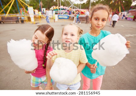 Cute girls eating cotton candy outdoors  - stock photo