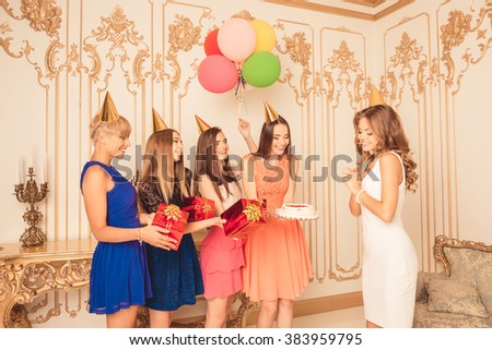 Cute girls give presents with balloons and birthday cake to their friends - stock photo